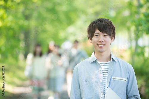 Obraz 新緑の中で微笑む大学生 - fototapety do salonu