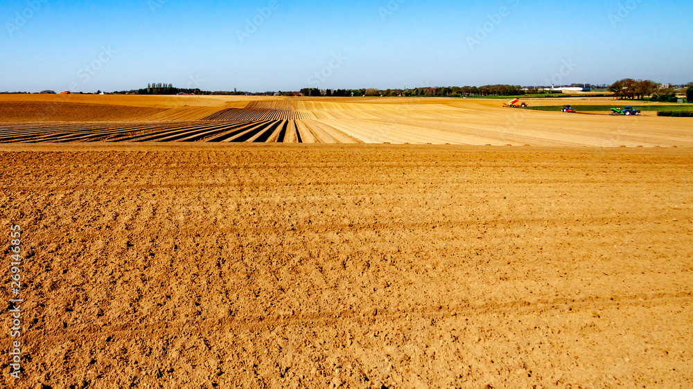 Fototapeta Agricultural land for planting vegetables with tractors in the background, with land for cultivation and land cultivated with potatoes on a sunny day in Oensel south Limburg in the Netherlands Holland