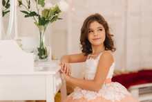 Little Girl Sits By The White Piano. White Flowers On The Piano. Girl Model In Beautiful Dress