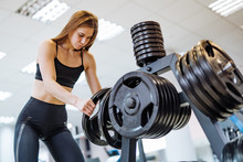 Concentrated Young Female In Black Sporty Wear Taking Barbell Disk In The Gym. Beautiful Fitness Lady Puts Barbell Plate Into Thespecial Stand After Healthy Workout.