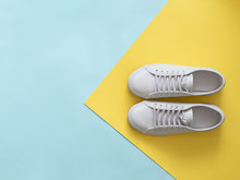 White Leather Sneakers On Blue And Yellow Background. Pair Of Fashion Trendy White Sport Shoes Or Sneakers With Copy Space For Text On Colorful Background. Overhead Shot Of New White Sneakers.Flat Lay