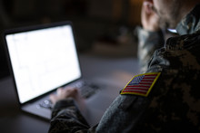 Soldier In Military Uniform Typing On A Computer. Focus On USA Flag.