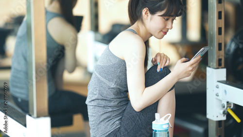 Foto  スマホを使う女性 フィットネスジム