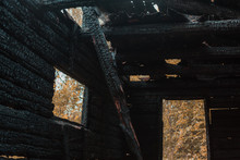 Burned Down House From The Inside, Wooden Black Beams Covered With Soot, Old House, After A Fire