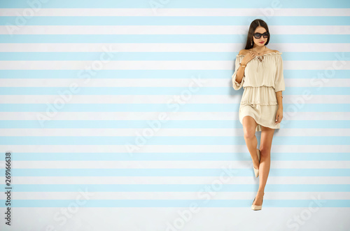 Fotografía  Slim young woman in summer dress and wall of blue and white color