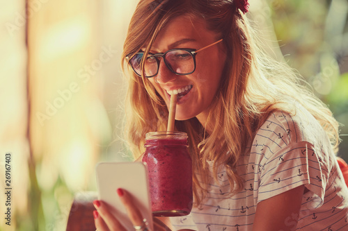 Fotografia  Beautiful woman using cellphone while drinking smoothie outdoors.