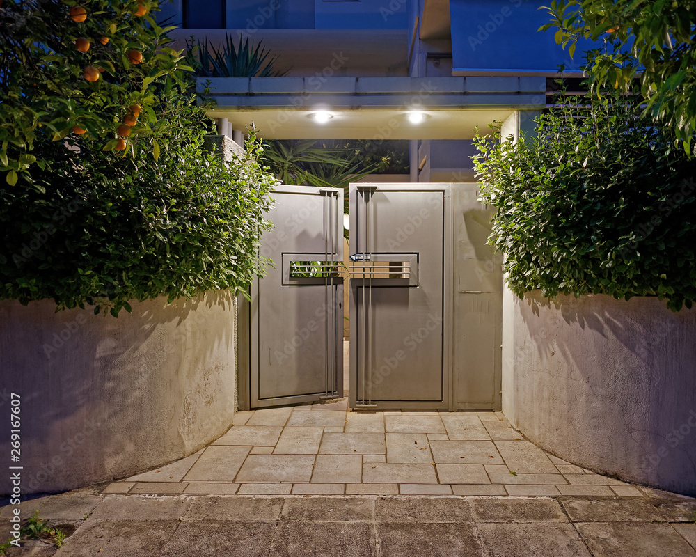 Fototapety, obrazy: contemporary house entrance metallic grey door late in the evening