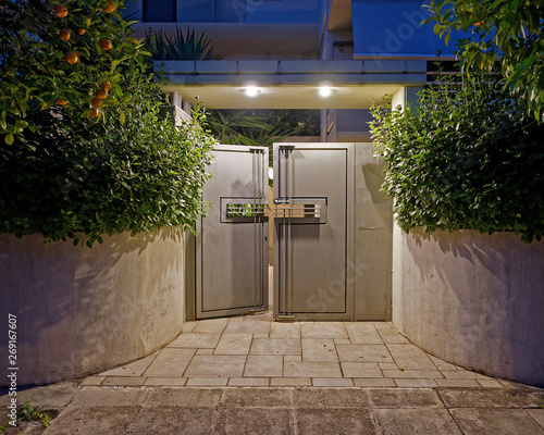 Fotografía  contemporary house entrance metallic grey door late in the evening
