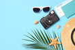 travel accessories and tropical leaves on a colored background top view.