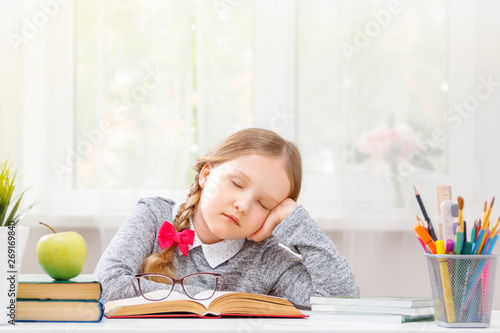 Little student girl sitting at the table, fell asleep at the books Wallpaper Mural