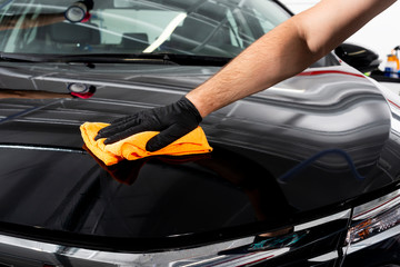 A man cleaning car with microfiber cloth. Car detailing or valeting concept. Selective focus. Car detailing. Cleaning with sponge. Worker cleaning. Car wash concept solution to clean