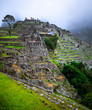 canvas print picture Amazing view of majestic Machupicchu temple landscape covered with fog on the background