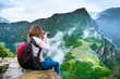 canvas print picture Girl with hiking rucksack sitting on the edge of the rock and taking amazing photos of breathtaking Machupicchu mountains landscape