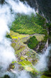 canvas print picture Aerial view of mountainious forested Machupicchu covered with clouds