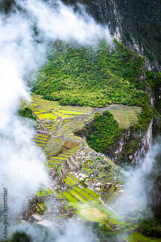 Foto  Aerial view of mountainious forested Machupicchu covered with clouds
