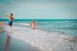 Leinwandbild Motiv little girl and boy run fly play with waves on beach