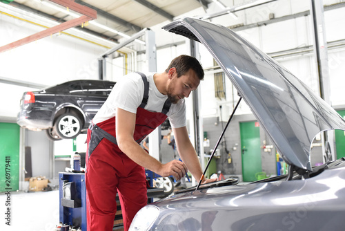 KFZ Mechaniker in einer Autowerkstatt - Diagnose der Motorelektronik - im Hintergrund Fahrzeug auf Hebebühne für Reparatur // Car mechanic in an auto repair shop - diagnosis of the engine electronics