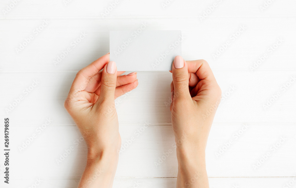Fototapety, obrazy: Woman holding white business card in hands. Tamplate for your design.