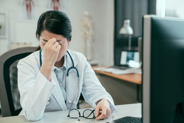 asian woman doctor sitting at desk with eyes closed and having headache after hard working day. young girl medical staff in white coat in clinic hospital hand taking glasses indoor frowning tired.