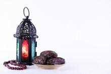Ramadan Food And Drinks Concept. Ramadan Lantern With Arabian Lamp, Wood Rosary, Dates Fruit And Lighting On White Background.