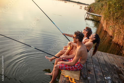 Poster Peche Group of friends sitting on pier by the lake and fishing.They joying in beautiful summer sunset.