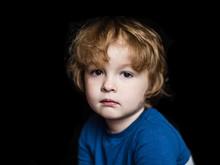 Portrait Of A Little Serious Sad Child On A Dark Background