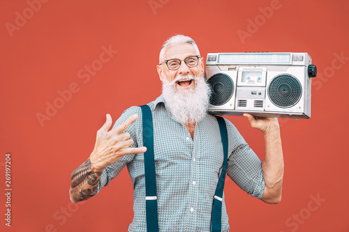 Fototapeta Happy senior man listening to music with boombox outdoor - Crazy hipster male having fun dancing with vintage stereo - Concept of elderly people lifestyle obraz