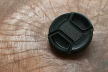 Black Camera Lens Cap For Protection On Wooden Board