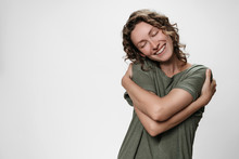 Young Curly Woman Hugging Herself, Looks Happy, Expresses Natural Positive Emotions