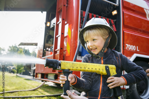 Little fireman holding firehose nozzle and splashing water. Canvas Print