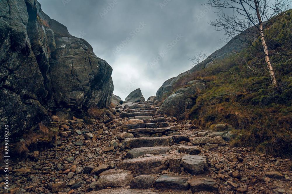 Fototapeta Stony path through the cliffs. Stony hiking trail in the mountains.
