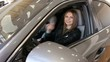 Portrait of a happy young girl driving a new car in a car dealership. The girl does not hide emotions sitting in her new car in the car shop.