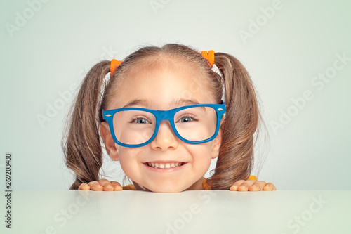 Obraz playful beautiful cute little girl smiling and hiding under table while looking at camera - fototapety do salonu