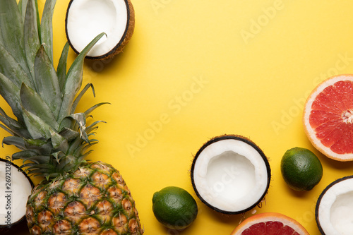 top view of whole ripe pineapple, citrus fruits and coconut halves on yellow background - 269212829
