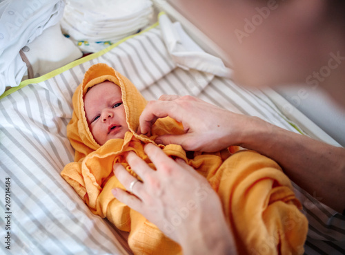 Photographie Unrecognizable father drying a newborn baby with a towel after bath at home