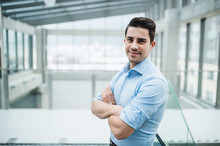 A Portrait Of Young Businessman Standing Indoors In An Office, Arms Crossed.