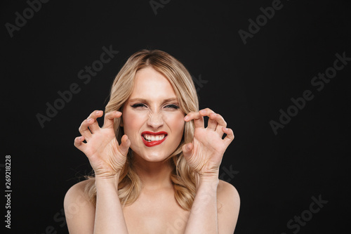 Blonde flirting growling woman with bright makeup red lips posing isolated over black wall background Tableau sur Toile