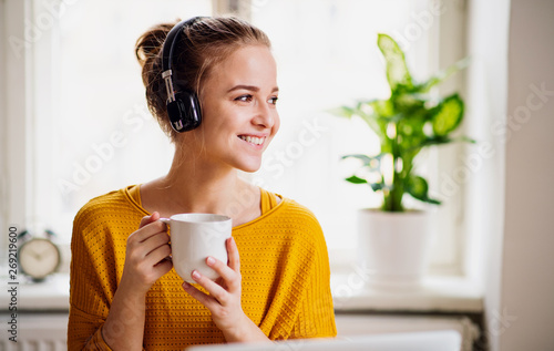 Foto  A young female student sitting at the table, using headphones when studying