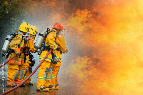 Firefighters spraying high pressure water to fire with copy space, Big bonfire in training, Firefighter wearing a fire suit for safety under the danger case.