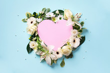 Creative Layout With White Roses, Lily, Gerbera, Pink Paper Heart Over Blue Background. Top View, Flat Lay. Spring, Summer Or Garden Concept. Flowers For Woman Day. Banner