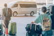 canvas print picture - Passengers with big roller luggage stand to wait for the car to pick up at airport arrival terminal.