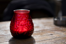 Red Glass With Candle On Wooden Table. Dark Background, Copy Space