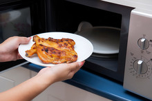 Women Hand Holding Food In A Microwave Oven
