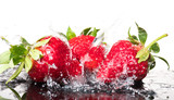 Several ripe wet red strawberries on white or colored background with splashes of water