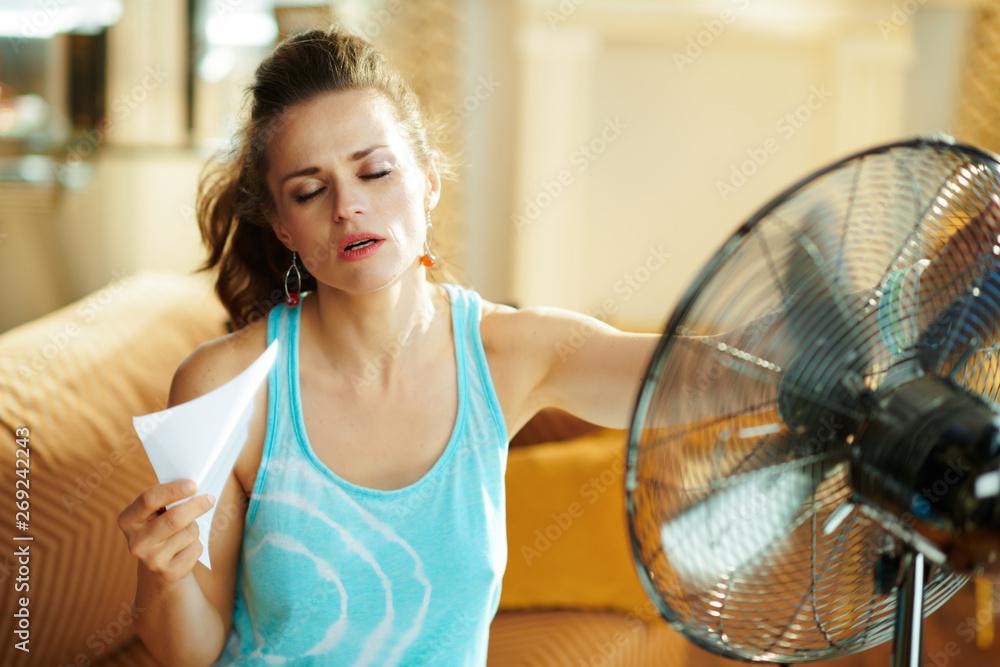 Fototapeta hot woman in front of working fan suffering from summer heat