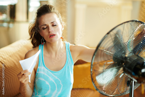 hot woman in front of working fan suffering from summer heat Tableau sur Toile
