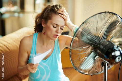 housewife in front of fan suffering from summer heat Fototapeta