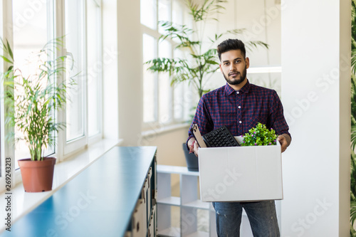 Shot of young professional man carrying cardboard box into his hand and moving into his new office Canvas Print