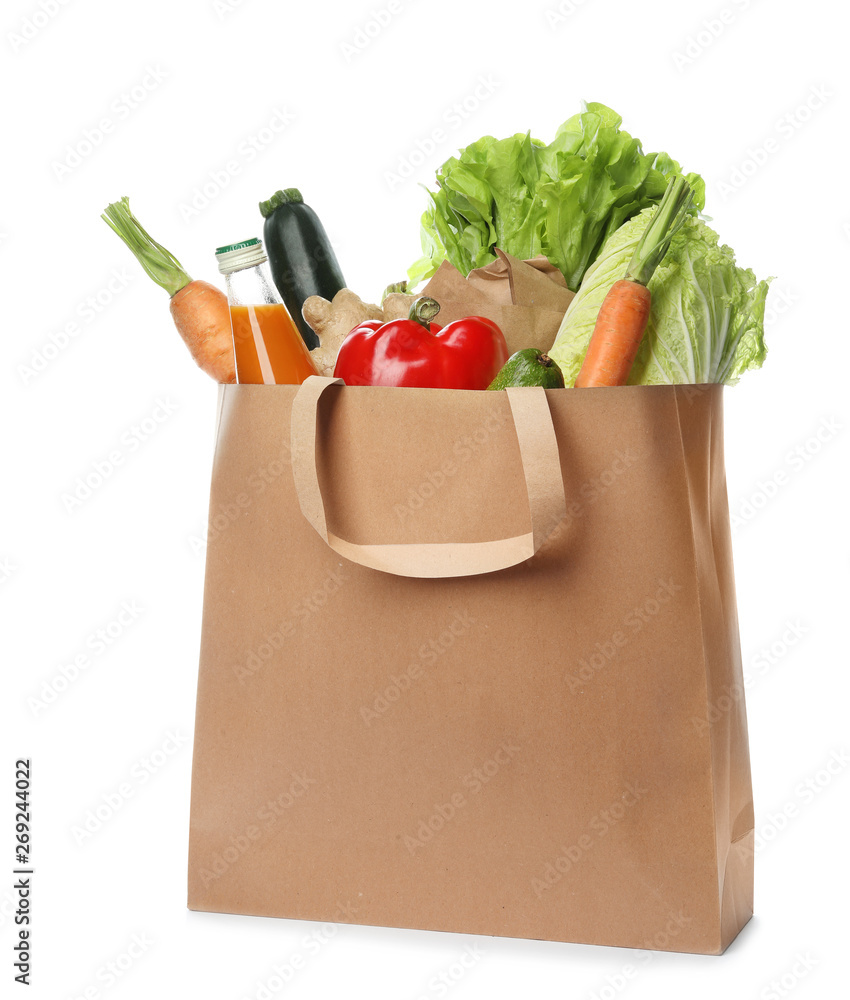 Fototapeta Paper bag with vegetables and bottle of juice on white background