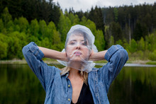 Girl With Cellophane Bag On Her Head Near The Lake And The Forest